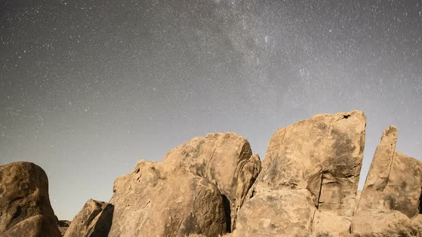 Stars and moonset, Alabama Hills. Time-lapse footage of stars rotating in the night sky over moonlit rocks in the Alabama Hills, California, USA. At the end of the clip, darkness falls over the rocks as the Moon sets. Rights-managed stock video