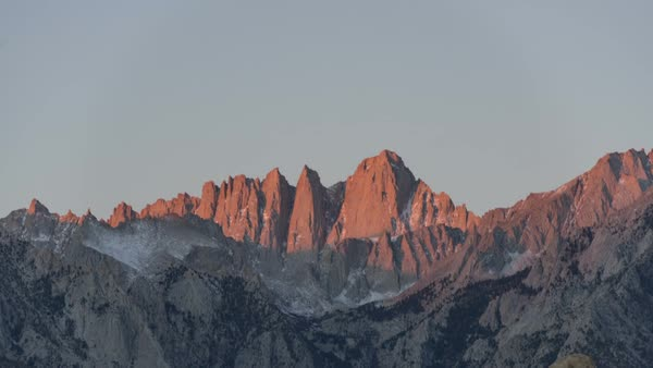 Time-lapse footage of alpenglow forming during sunrise on the tall sheer granite faces of Mount Whitney in the Sierra Nevada, California, USA. Rights-managed stock video