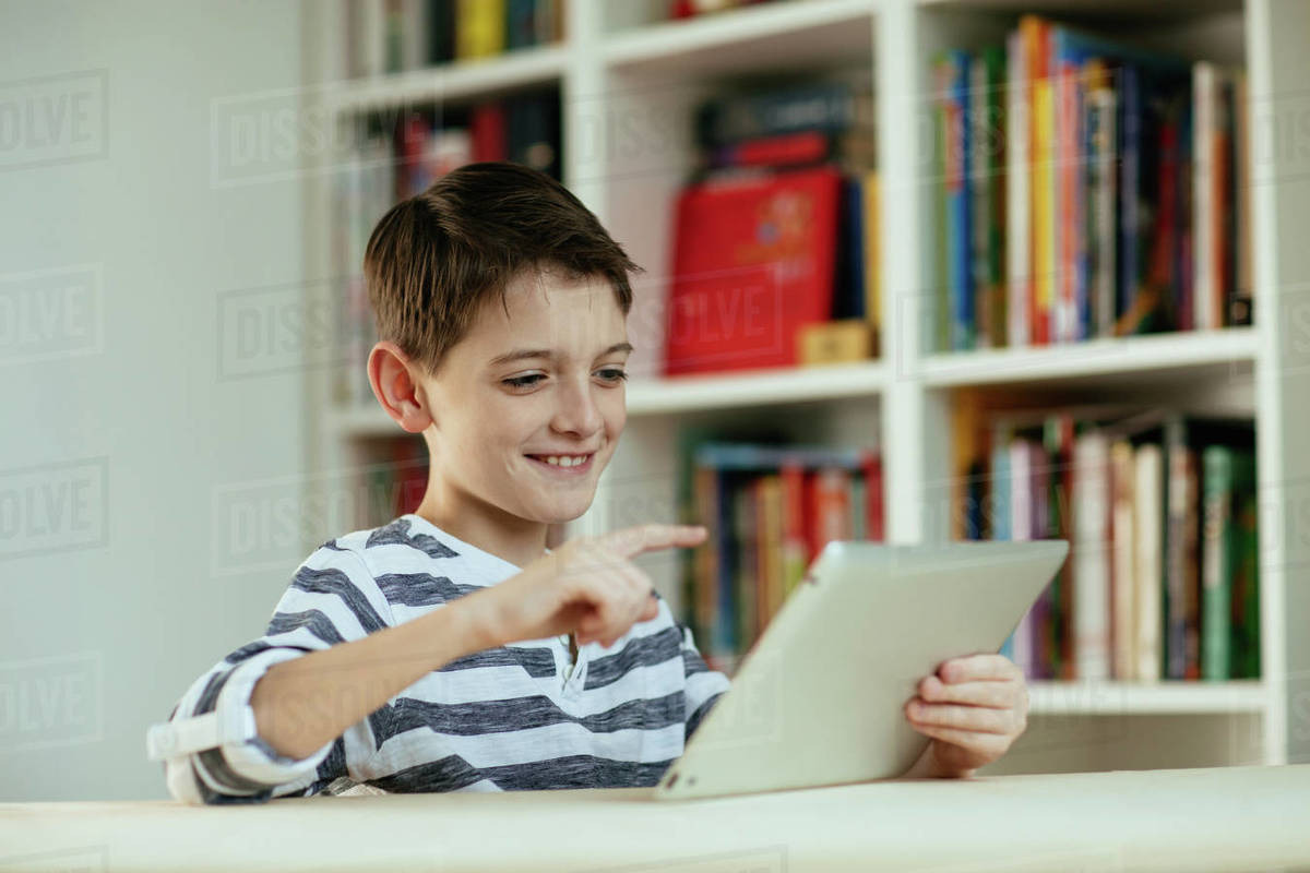 Young boy using digital tablet. Portrait of cheerful boy using digital tablet at home smiling. Royalty-free stock photo