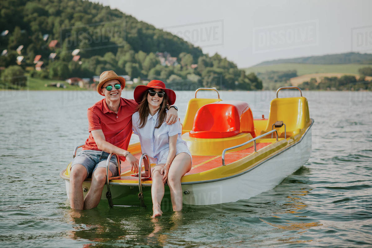 Front view of smiling young couple sitting on pedal boat. Portrait of man and woman in love enjoying boating on the lake. Royalty-free stock photo