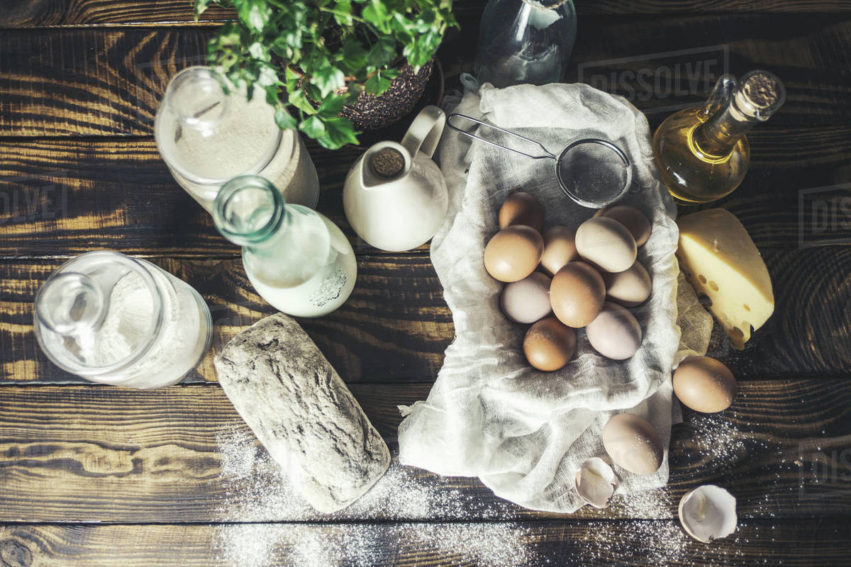 Top view of eggs, milk, cheese and bread on wooden table. Royalty-free stock photo