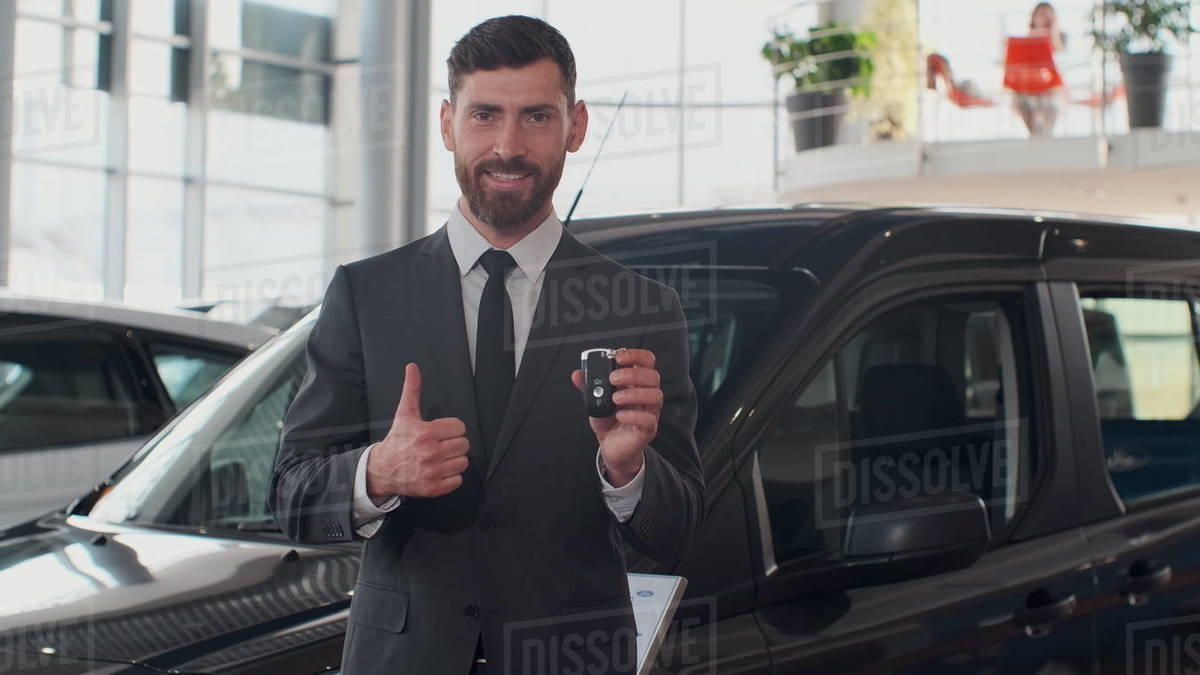 Professional car salesman smiling happily holding car keys standing in front of new cars at the dealership Royalty-free stock photo