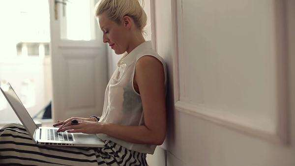 Blonde Caucasian woman sitting on the floor and working on her laptop at home. Royalty-free stock video