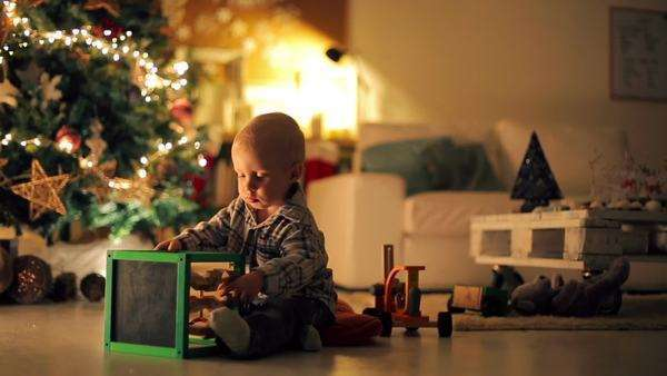 Adorable Caucasian boy playing by the Christmas tree. Royalty-free stock video
