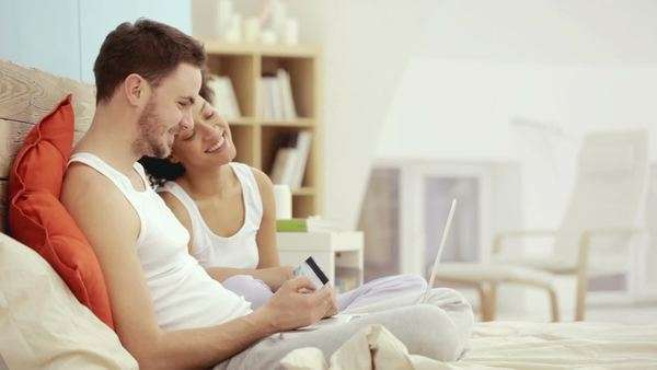 Smiling multiethnic couple sitting in bed and shopping online. Royalty-free stock video