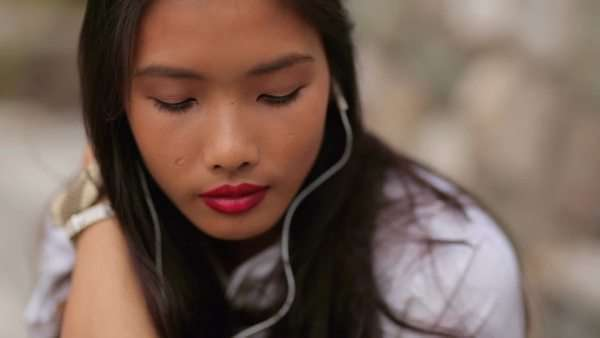 Happy young Asian woman listening to music outdoors. Royalty-free stock video