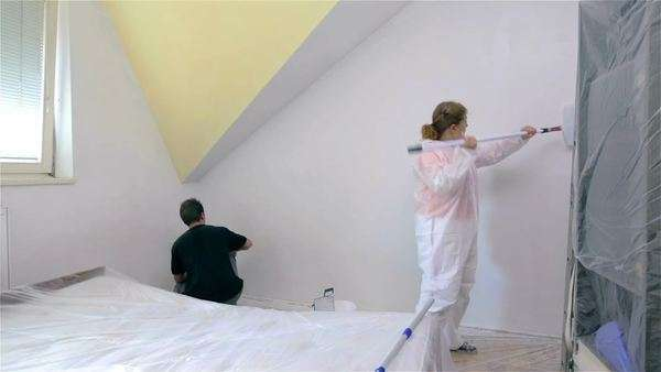 Two person paint room with white color. DIY painting home walls by yourself. Couple man and woman adding fresh paint on walls. Royalty-free stock video