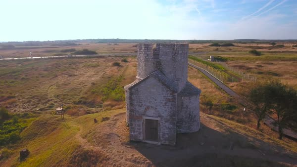 Flying around medieval St. Nicholas church in Croatia. Low jaw flight around historical abandoned church on top of little hill at sunrise. Church in front with landscape in background. Royalty-free stock video