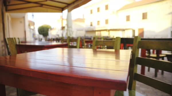 Outdoor restaurant wooden table jaw shot. Camera on gimbal stabilizer sliding around a table with two chairs, blurred background. Close up on colorful table. Royalty-free stock video