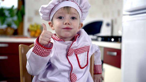 Young cook in kitchen preparing Valentines cookies for his loved ones. Making, baking and decorating heart shaped cookies. Royalty-free stock video
