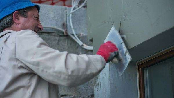 Putting A Coat Of Cement On Wall. Professional Masonry Working On A New  House Outside