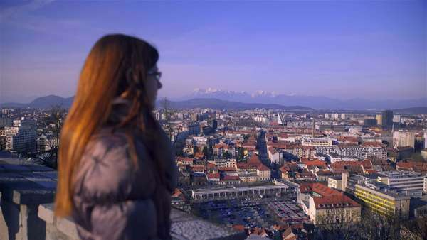 Woman observing Ljubljana city scape. Woman standing very high above the Ljubljana city, view from castle, looking city scape on a sunny day. Royalty-free stock video