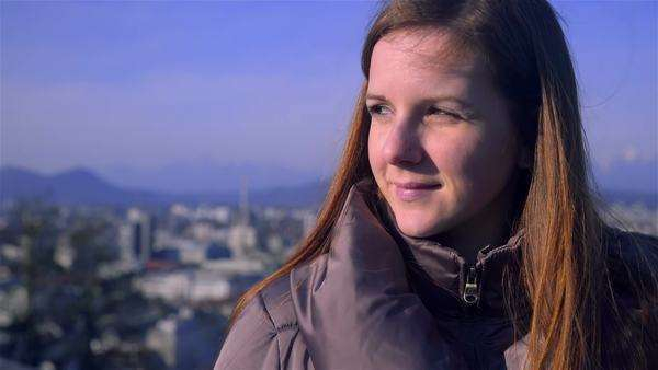 Young woman looking in distance above city. Portrait shot of female person with long brown hair standing above city scape looking towards the sun of camera. Royalty-free stock video