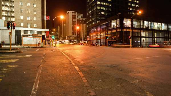 Linear timelapse moving up at a busy intersection at night with traffic and people crossing in Ghandi Square, mid city Johannesburg, South Africa Royalty-free stock video