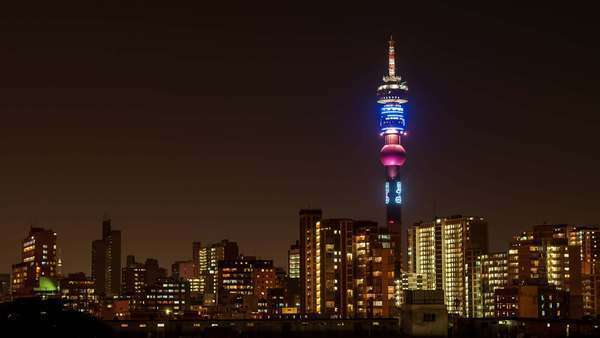 Static medium timelapse of the Hillbrow Tower, over the city centre of Johannesburg at night with flickering lights of apartments and flats Royalty-free stock video