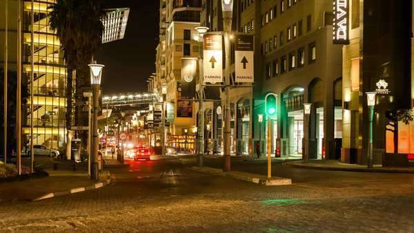 Static timelapse at a busy intersection of the nightlife and people buzzing in Johannesburg, South Africa at the Sandton Convention Centre Royalty-free stock video