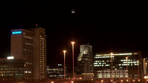 Time lapsed long shot of Cape Town city at night, moon setting over city Rights-managed stock video