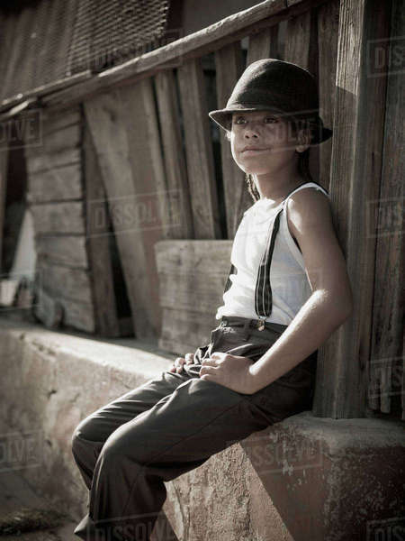 Young retro boy sitting against wall, Sophiatown, Cape Town, Western Cape Rights-managed stock photo