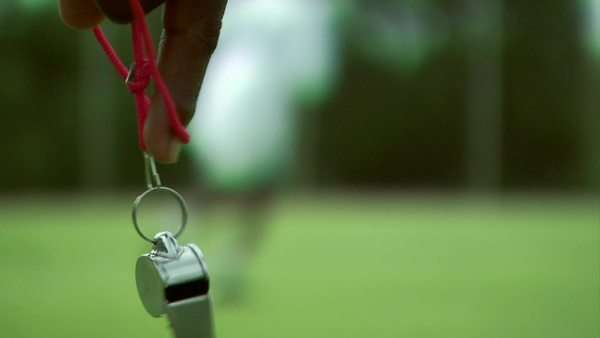 Close up of a whistle dangling from a man's hand during a soccer match Rights-managed stock video