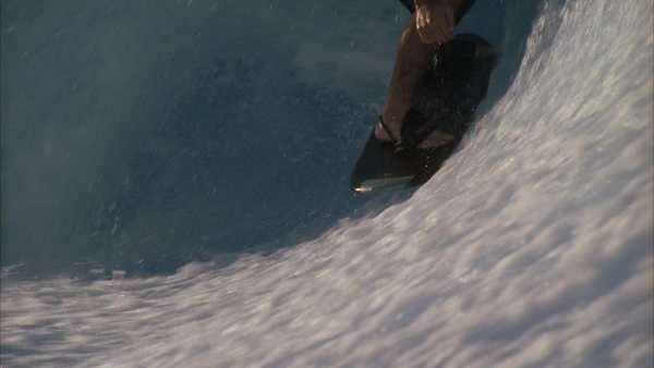 Slow motion of a surfer riding up and getting airborne on a wave made from a wave machine Rights-managed stock video