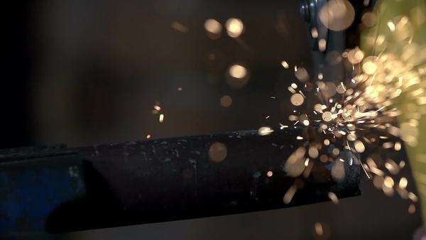 Cutting, slitting and polishing metal tube with electric grinder with numerous sparkles flying around shot in slow motion Royalty-free stock video