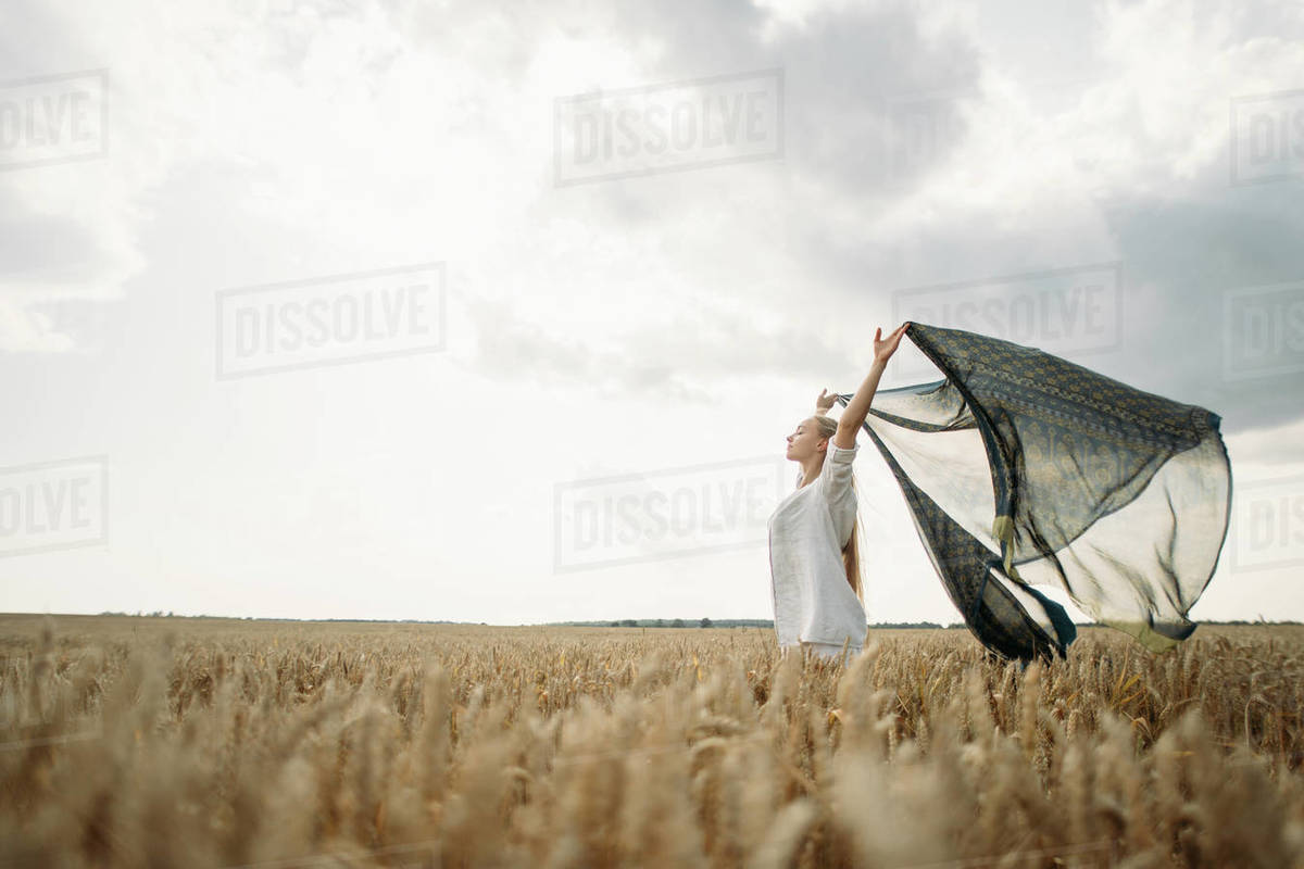 young long-haired woman standing in a wheat field Royalty-free stock photo