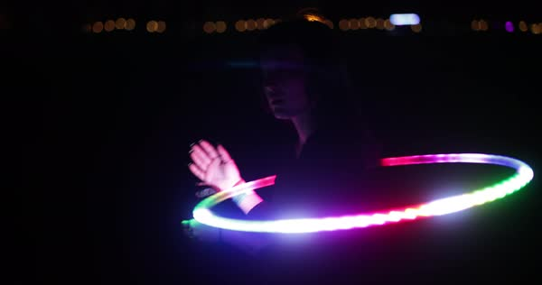Hand-held shot of a woman dancing with an LED hula hoop Royalty-free stock video
