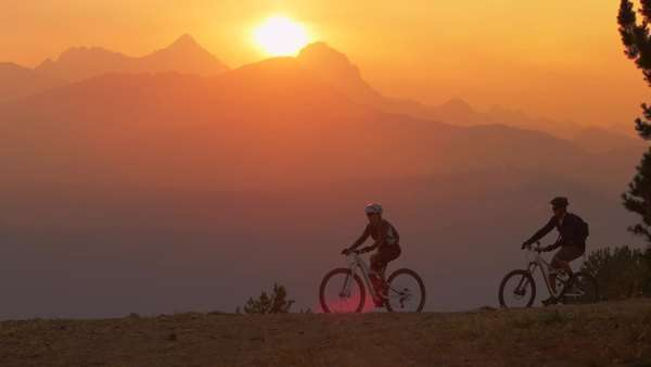 Two mountain bikers pull to a stop on a hillside at sunset Royalty-free stock video