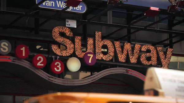 A lit up subway sign sparkles above a busy street in New York City Royalty-free stock video
