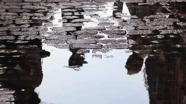 Pedestrians are reflected in a puddle on a street in New York City Royalty-free stock video