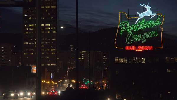 A wide establishing shot at night of the neon sign welcoming visitors to Portland, Oregon. Royalty-free stock video
