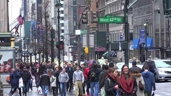 People walk on a street in Midtown Manhattan in the rain with traffic passing. Royalty-free stock video