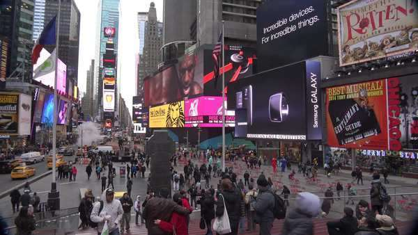 Pan across crowds of people and bright neon advertisements in Times Square, New York City. Royalty-free stock video