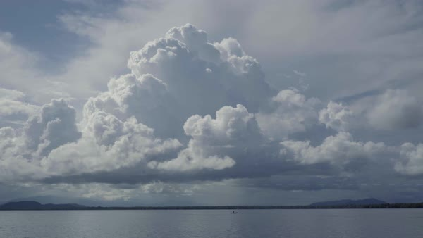 Huge storm clouds loom behind a canoe moving in the distance across Lake Guatemala. Royalty-free stock video