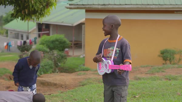 An african boy plays a pink guitar in Uganda. Royalty-free stock video