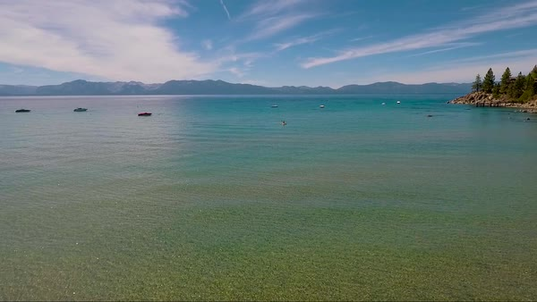An aerial over a woman paddling a kayak across Lake Tahoe. Royalty-free stock video