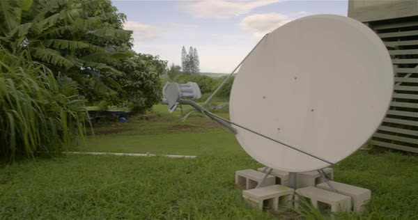 Panning shot reveals a satellite dish behind a communication center. Royalty-free stock video