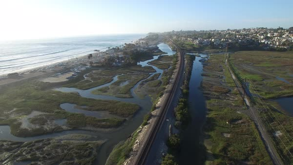 High aerial over an Amtrak train traveling beside the Pacific ocean near San Diego. Royalty-free stock video