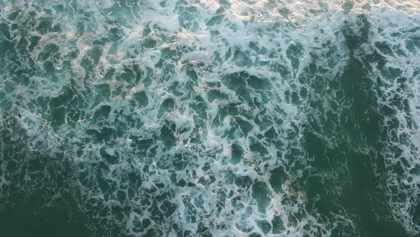 Aerial perspective looking straight down at the ocean with waves rolling in. Royalty-free stock video