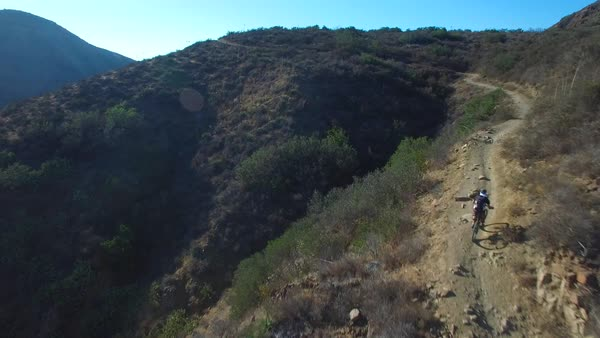 Good aerial following a mountain biker ascending a California mountain. Royalty-free stock video