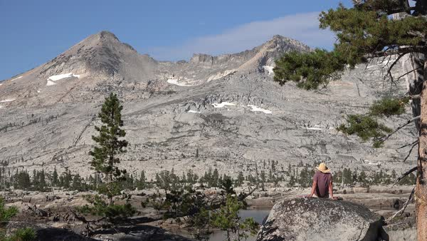 A man sits on a rock overlooking the Desolation Wilderness in the Sierra Nevada mountains California. Royalty-free stock video