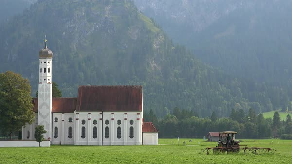 Establishing shot of a traditional German Bavarian church with a tractor plowing fields foreground. Royalty-free stock video