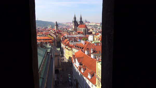 High angle view through narrow church belfry over the rooftops of Prague, Czech Republic. Royalty-free stock video