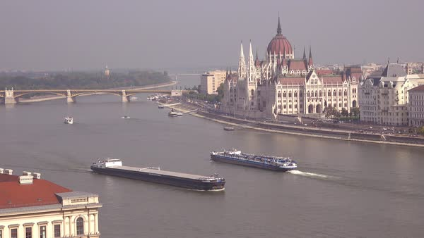Budapest Hungary and Parliament as barges move along the Danube River. Royalty-free stock video