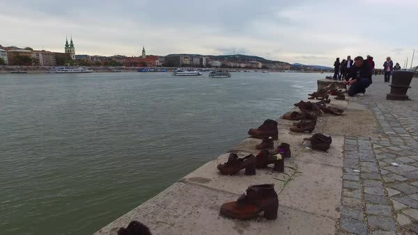 Visitors remember victims of the Holocaust at the Shoes Along The Danube Memorial in Budapest, Hungary. Royalty-free stock video