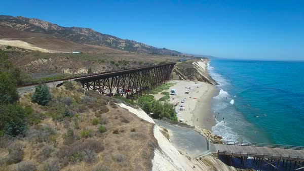 A beautiful aerial over a train crossing a bridge along the Pacific Ocean. Royalty-free stock video