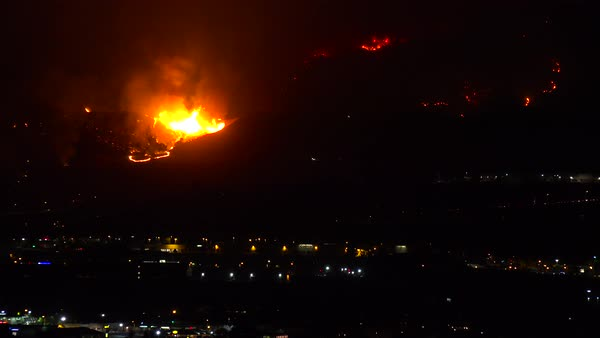 Out of control wildfire burns behind a California city at night. Royalty-free stock video