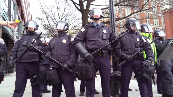 Police in riot gear form a line to confront protestors at Trump's Inauguration in Washington DC. Royalty-free stock video