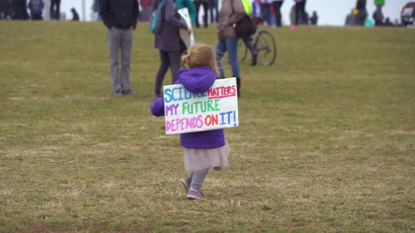A little girl runs around with a sign on saying that science matters at an anti-Trump rally in Washington D.C. Royalty-free stock video