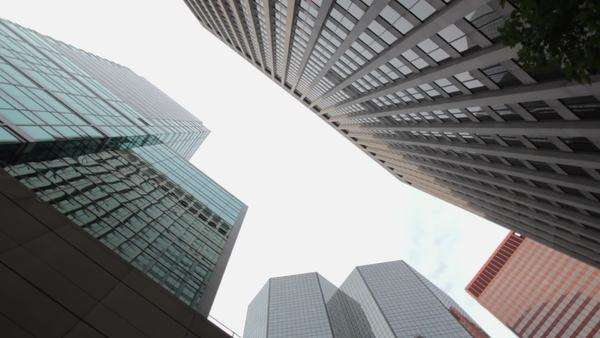 A low-angle view of several tall office buildings in the city as the camera slowly rotates 180 degrees. Wide shot with rotating camera movement. Royalty-free stock video